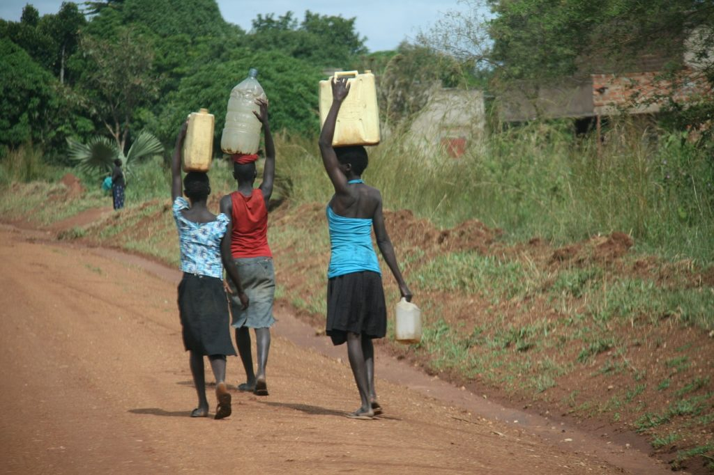 Three women carrying water in canisters on their heads